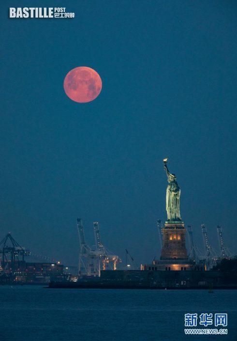 5月26日,在美國紐約,一輪圓月出現在自由女神像上方的天空。