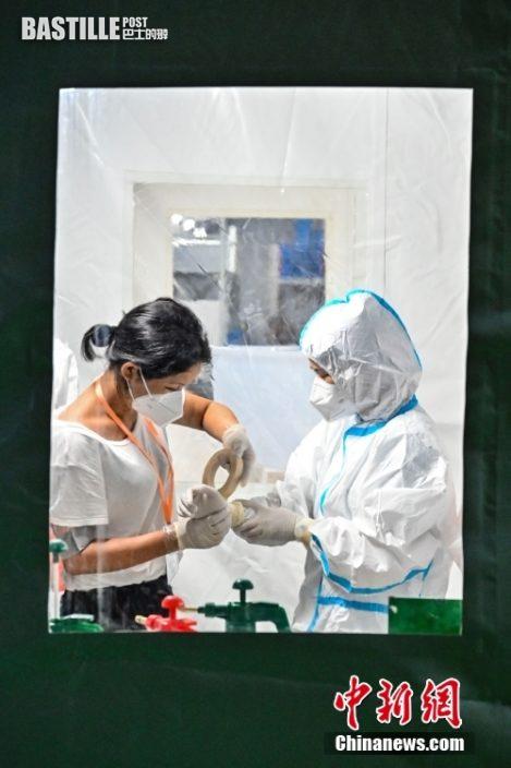 6月3日晚,廣東省廣州市廣州體育館,由廣州實驗室聯合國家呼吸醫學中心、廣州呼研院、金域醫學等單位聯合共建的四組「獵鷹號」氣膜實驗室全部啟用,四組「獵鷹號」氣膜實驗室日核酸樣本檢測產能可達12萬管。圖為工作人員在「獵鷹號」氣膜實驗室內穿戴防護服。 中新社記者 陳驥旻 攝