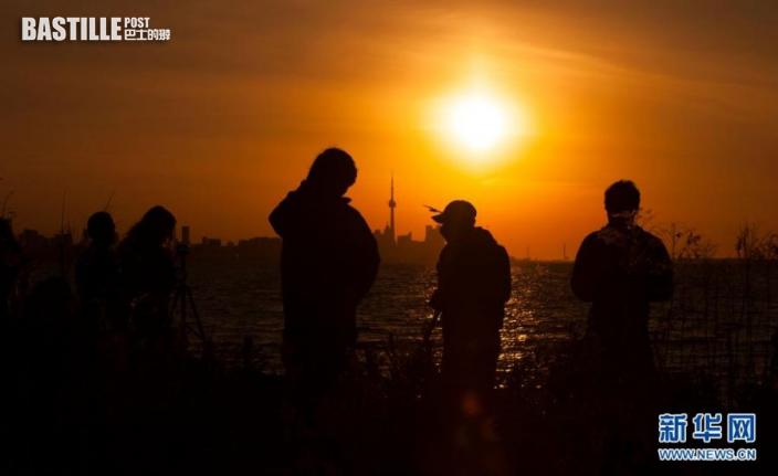 6月10日,人們在加拿大多倫多安大略湖邊拍攝日出時分出現的日食。
