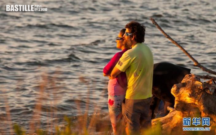 6月10日,人們戴著日食眼鏡在加拿大多倫多安大略湖邊欣賞日出時分出現的日食。