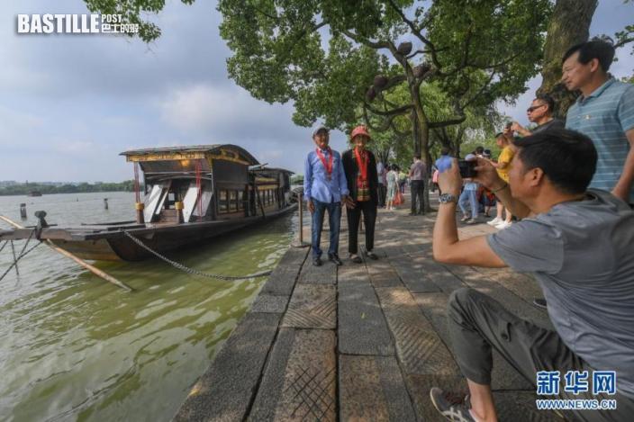 7月1日,兩名老黨員在浙江嘉興南湖湖心島停泊的南湖紅船旁拍照留影。新華社記者 徐昱 攝
