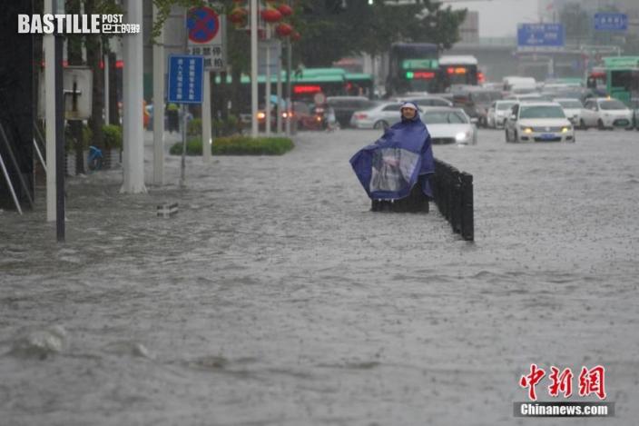 7月20日,河南鄭州,市民冒著暴雨出行。