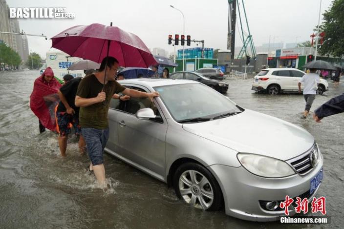 7月20日,河南鄭州,一車輛經過積水路段後拋錨,眾人幫忙將其推出。