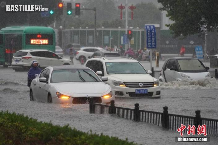 7月20日,河南鄭州,車輛經過積水路段。