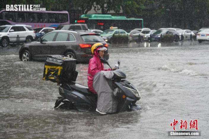 7月20日,河南鄭州,一名外賣騎手在積水中前行。