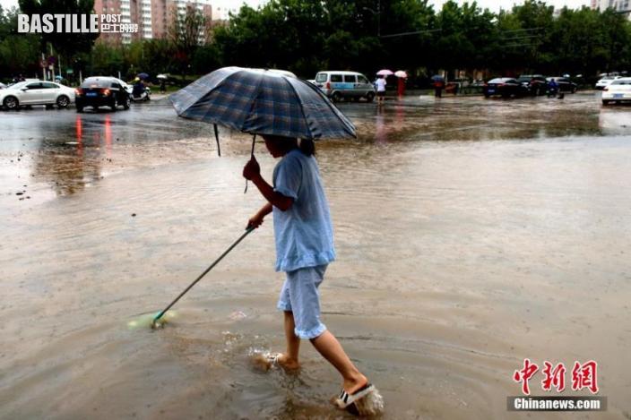 2021年7月21日,一居民手持棍棒探路前行,以防掉入水坑。