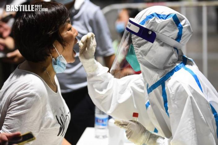 7月21日晚,在南京市玄武區一處檢測點,醫務人員在為市民進行核酸檢測取樣。