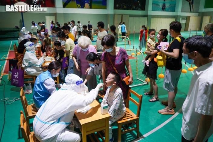 7月21日晚,在南京市建鄴區一處檢測點,醫務人員在為市民進行核酸檢測取樣。