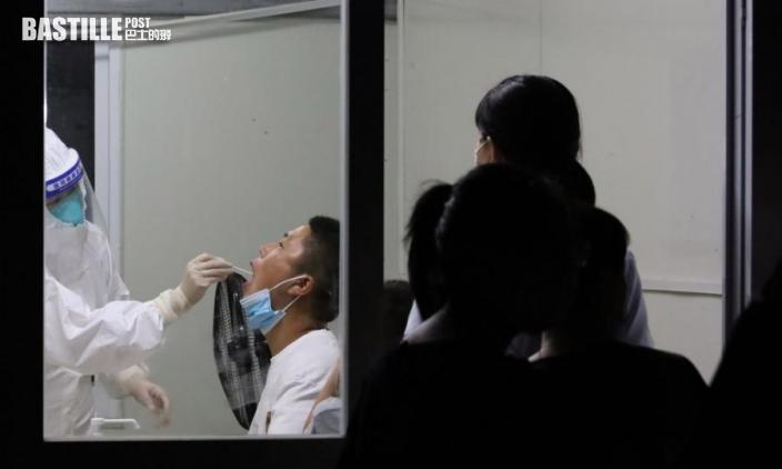 7月21日,在南京市溧水區人民醫院,醫務人員為市民進行核酸檢測取樣。