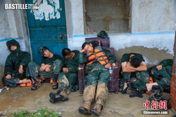 7月21日,武警官兵在搶險救災一天一夜後,躺在地上休息。