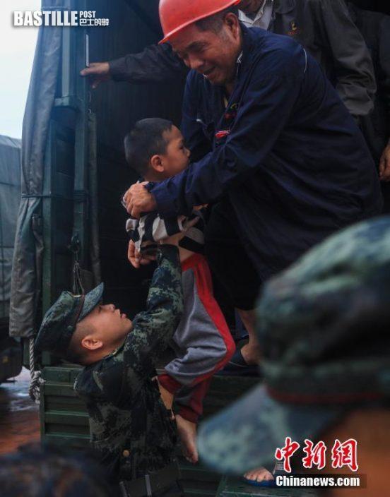 7月20日,武警官兵在河南省登封市告成鎮轉移受災民眾。