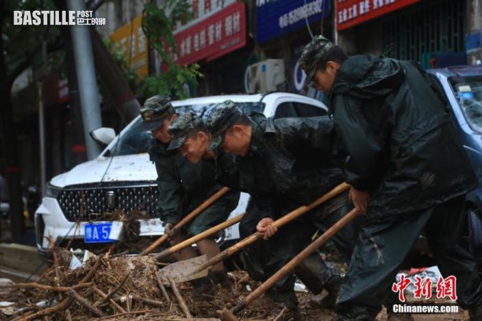 7月21日,武警官兵在河南省鞏義市米河鎮街道上清理雜物。