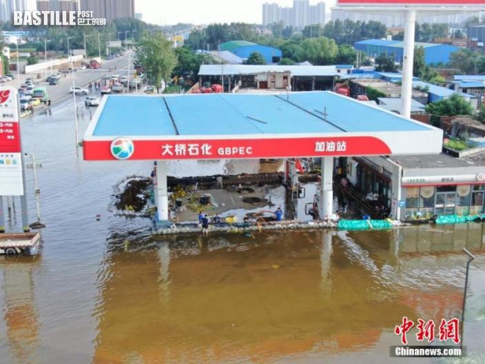 圖為一加油站自築堤壩抵擋洪水。