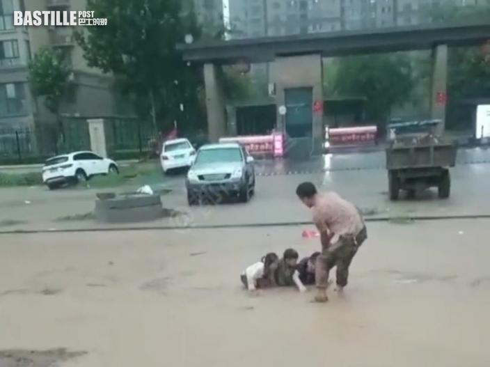 鄭州暴雨水淹車頂 路人游泳砸窗救出被困1大1小
