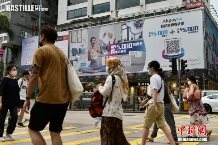 8月1日,香港特區政府向市民發放第一期2千港元電子消費券,位於尖沙咀一商場、零售商戶推出不同的優惠,吸引大量市民入內消費。圖為尖沙咀戶外廣告提醒市民登記領取消費券。 中新社記者 李志華 攝