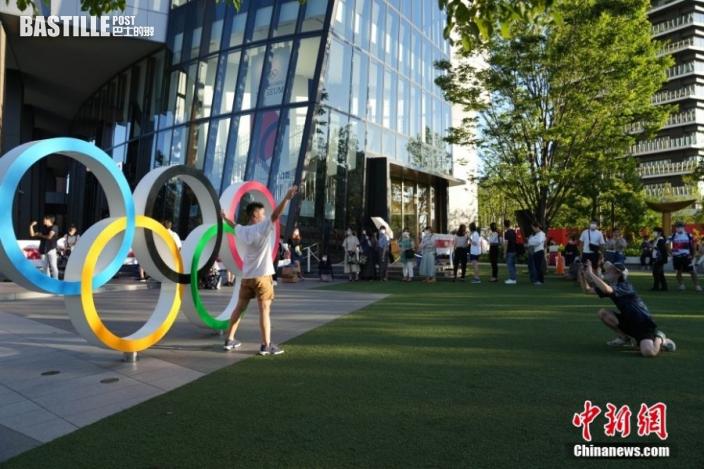 8月3日,日本東京國立競技體育場外,日本民眾排隊與五環合影。因疫情影響,日本首都圈地區舉行的奧運會賽事全部以無觀眾形式舉行。 中新社記者 韓海丹 攝