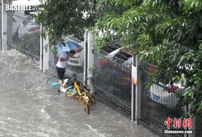 市民沿著小區欄杆走過積水路段。