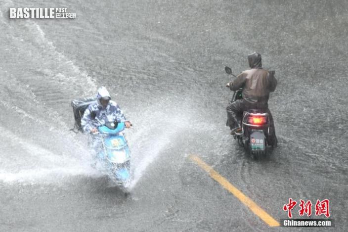 市民在積水路段騎車出行。