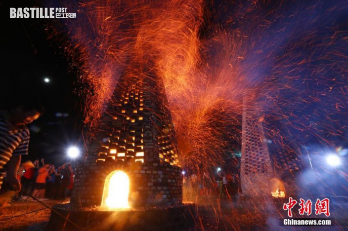 塔下裝柴點火,火苗時而躥出塔身,時而躥過塔頂,眾人圍觀歡呼。圖:中新社