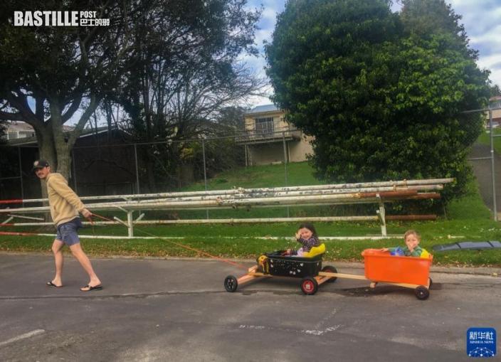 9月17日,在紐西蘭奧克蘭,兩個孩子坐在爸爸自製的簡易拉車「車廂」里在街上兜風(手機拍攝)。「車廂」是家裏的置物筐,框架是簡易的木條,六個大小不一的輪子是從不同推車上拆下拼湊的。即便如此,大人孩子均自得其樂。圖:新華社