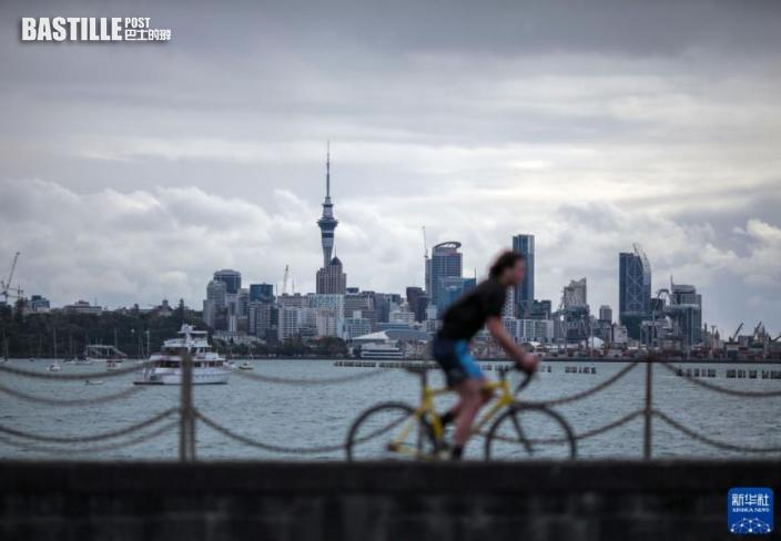 9月19日,一名男子騎車從紐西蘭奧克蘭使命灣海邊經過,背景是奧克蘭市中心。圖:新華社