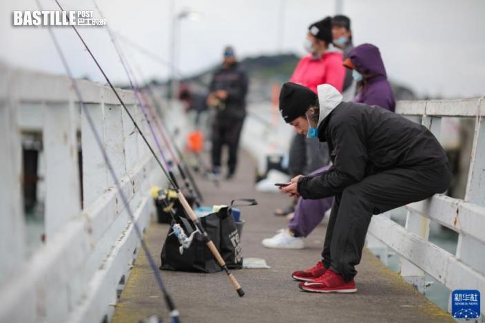 9月19日,在紐西蘭奧克蘭東區使命灣的一個碼頭,人們戴著口罩,保持距離一字排開釣魚。圖:新華社