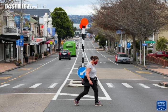 9月19日,一名女子戴著口罩穿過以往熱鬧繁華的紐西蘭奧克蘭帕內爾街。圖:新華社