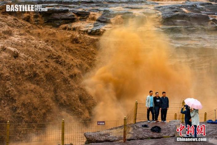 圖為遊客在側瀑布前拍照留念。
