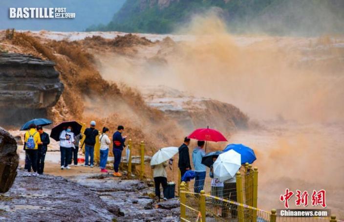 圖為遊客觀賞波濤洶湧的壺口瀑布。